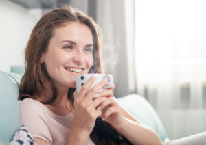 Smiling woman sitting on couch at home and drinking coffee,