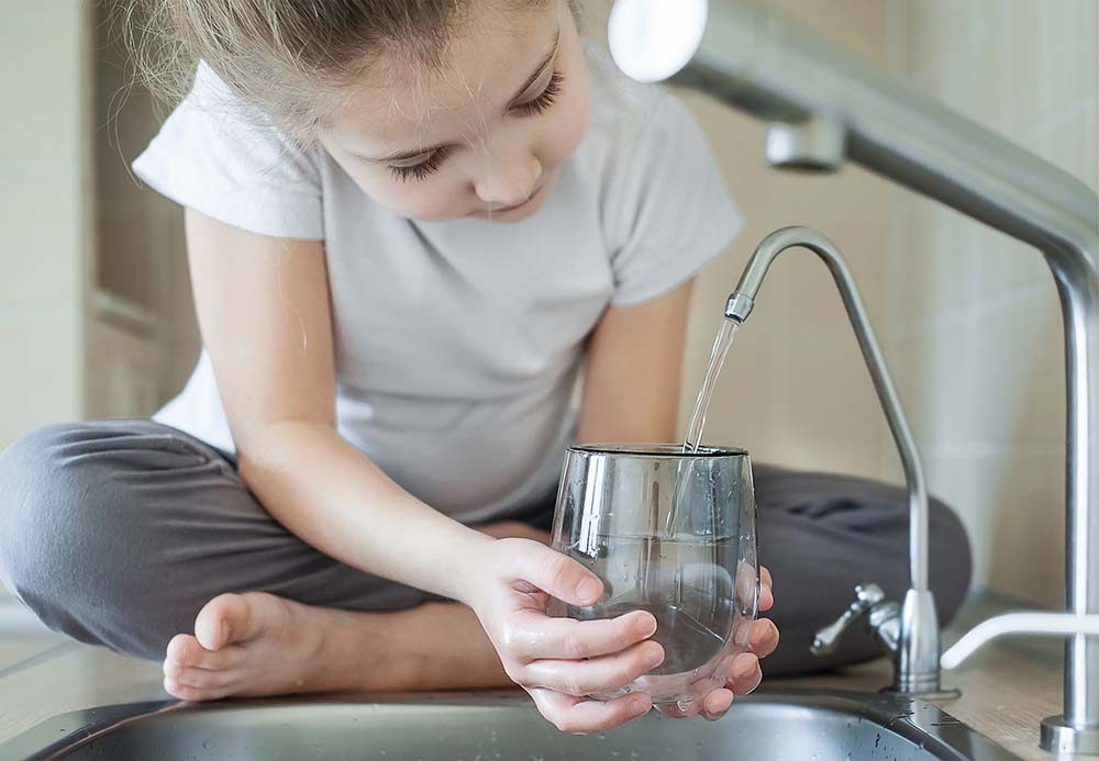 Girl Drinking from a reverse osmosis drinking system