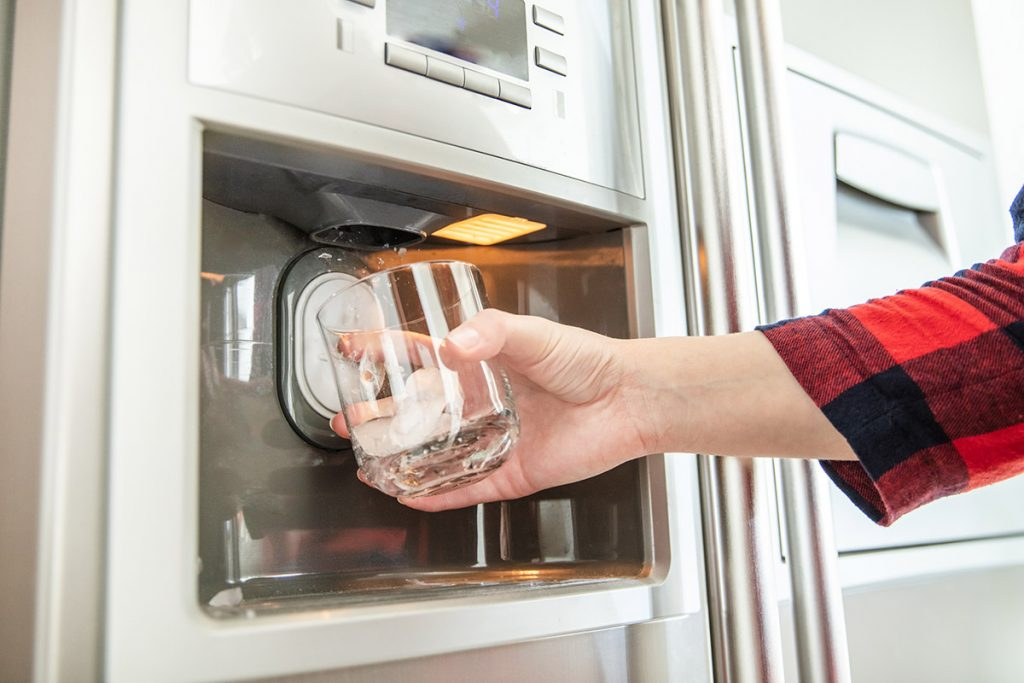 Woman's hand holds glass and uses refrigerator to make fresh clean ice cubes.